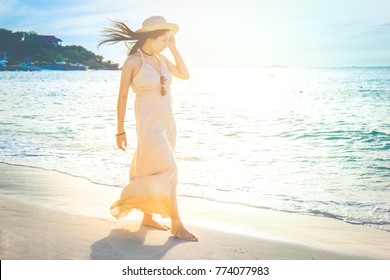 Woman in a cream dress is walking, enjoying the beautiful sunset on the beach.Soft focus