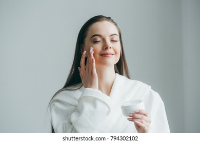 Woman cream face in bathrobe with beauty healthy skin at home natural portrait