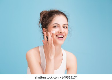 Woman with cream on blue background