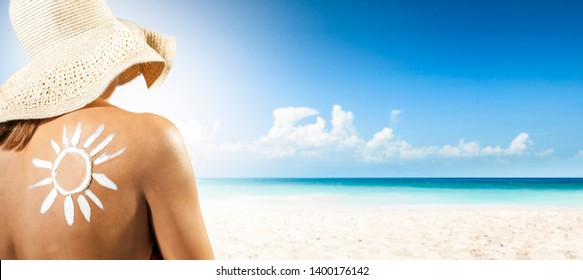 Woman with cream and summer background of beach. Free space for your decoration.