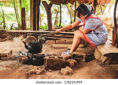 A woman is creating an ancient fire to boil fresh coffee in Mae Klang Luang Village, Thailand, 16 July 2020, Mae Klang Luang Village, near Chiang Mai, Thailand.