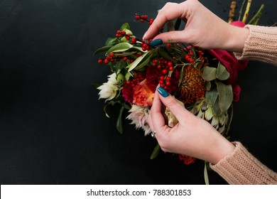 Woman creating autumn flower arrangement on dark background. Bouquet design and composition art ikebana.