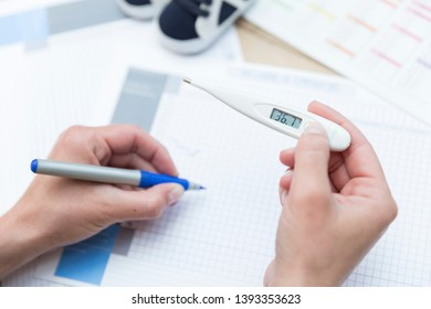 Woman creating a temperature chart to identify the day she ovulates.