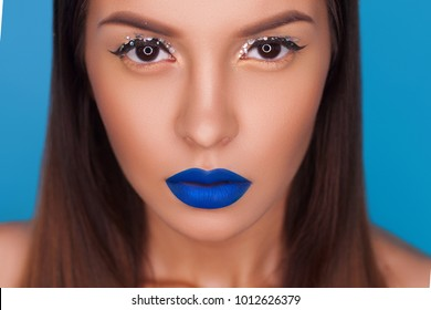 woman with creative fashion make-up with blue lips
