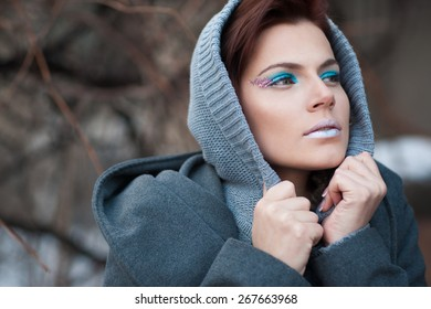The woman with a creative make-up wraps up in a gray coat