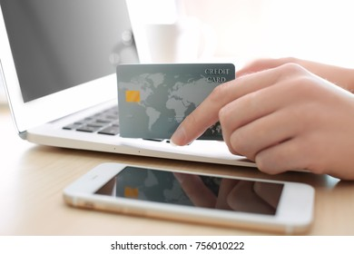 Woman with credit card and laptop at table, closeup