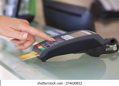 Woman with credit card swipe through terminal, security code