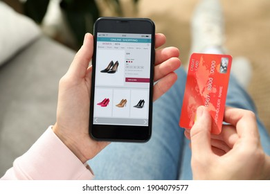 Woman with credit card using smartphone for online shopping indoors, closeup