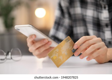 Woman with credit card using smartphone for online shopping at white table, closeup