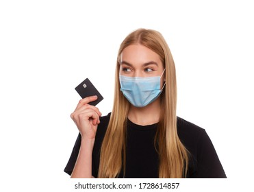 woman with credit card wearing a medical mask isolated on a white background. Conceptual photo, purchases with cashless payment during quarantine.