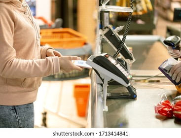 A woman is credited to the store at the checkout from her phone.
