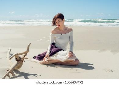 Woman in a crib sitting on the seashore