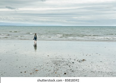 Woman at Criccieth beach in Wales, UK