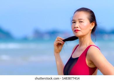 Woman with crimson bikini enjoy on beach at Ban Krut Beach, Prachuap Khirikhan Province Thailand