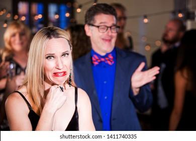 Woman cringing with boorish man