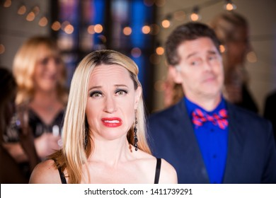Woman cringing with disappointing man