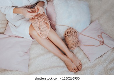 Woman crocheting on the bed in the morning with pink wool yarn, crafts hobby, handmade