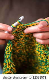 Woman crochets. Handwork. Crochet hook. Female hands closeup. Female hands hold the hook. Vintage carpet. Knitted plaid. Handmade. Home hobby.