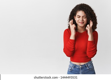 Woman cross fingers good luck praying intense close eyes purse lip seriously dreaming achieve goal waiting important results making wish fulfil desire, standing white background anticipating