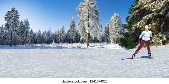 A woman at cross-country skiing or langlauf running in the wintry forest