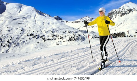 A woman cross-country skiing in the wintry apine landscape