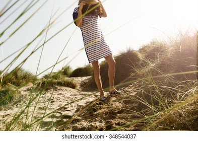 Woman crosses sand dunes at sunset in summer wear