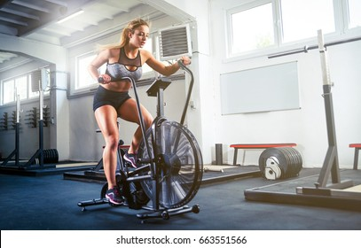 Woman at the crossfit gym using exercise bike for cardio workout