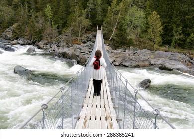 Woman crossing a foaming stream on a suspension bridge