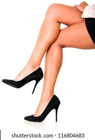 Woman crossing legs and wearing high-heels isolated over white
