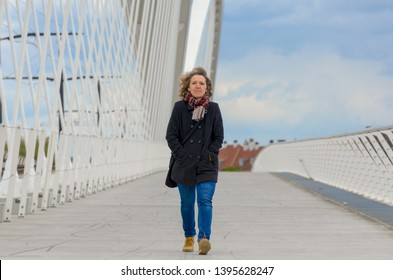 Woman crossing a pedestrian bridge on a cold day wearing coat and knitted scarf walking towards the camera in a receding perspective