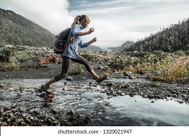 Woman crossing the river in the wild valley