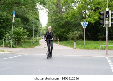 Woman crossing road on a traffic light with e-scooter