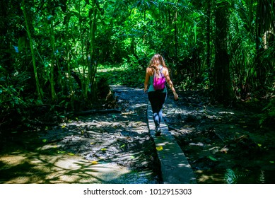 Woman crossing small river over wooden plank in Corcovado National Park, Costa Rica.