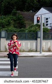 woman crossing the street on red light while watching the mobile phone
