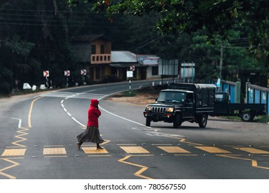 Woman crossing the street at the yellow pedestrian crossing in red coat