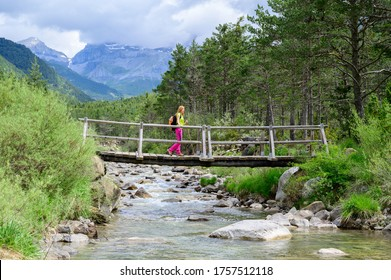 Woman crossing a wooden bridge over the river in the mountains. River Estarrum.Aisa.Huesca.Spain.