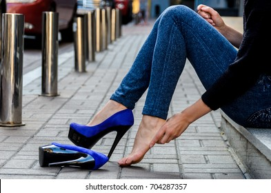 The woman crouched on the porch near the house and took off her uncomfortable shoes, which caused her pain and rubbed calluses