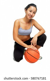 Woman crouching on floor, hand on basketball