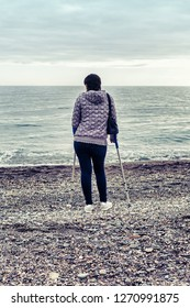 Woman with crutches at the beach