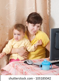 Woman with crying baby working  with computer at home