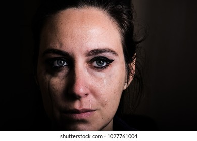 Woman crying with light eyes with blurred makeup