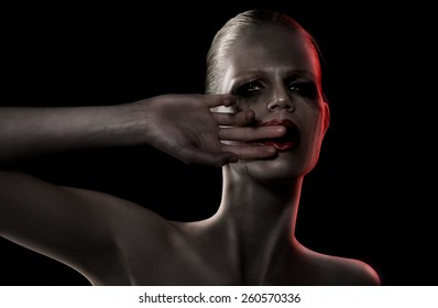 Woman crying. Red gel used on strobe. Skin manipulated into dark.