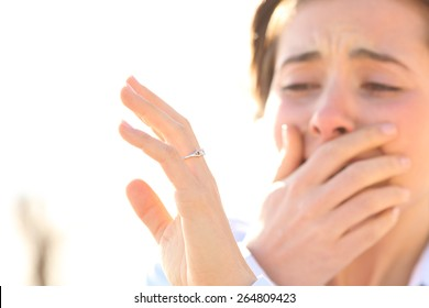 Woman crying while watching an engagement ring after proposal in a sunny day