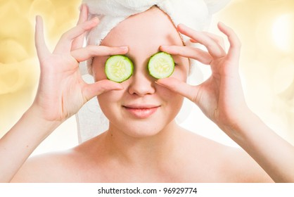 Woman with cucumbers on eyes with lights in the background