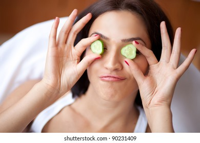 Woman with cucumbers smiles