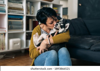 woman cuddling with her dog at home