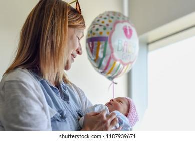 woman cuddling newborn baby in hospital