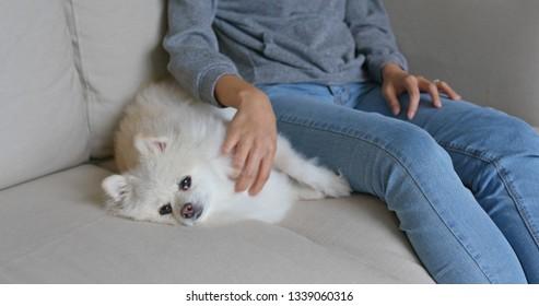 Woman cuddling on her pomeranian dog