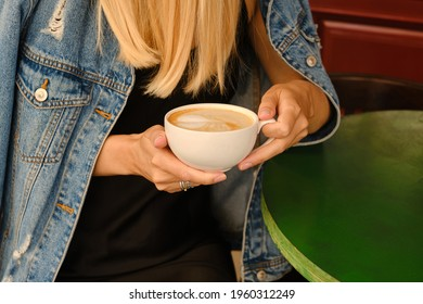 Photo of Woman with a cup of aromatic coffee in her hands sits on the summer terrace of the restaurant. The girl drinks coffee after breakfast. Delicious hot latte in a white cup. Quiet freelance lifestyle