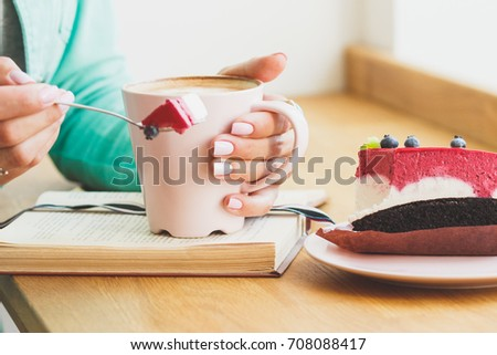 Woman with a cup of cappuccino and a piece of dessert on the plate, soft focus background